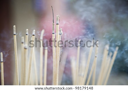 Yellow incense sticks burning in an altar at a Taoist temple - stock photo