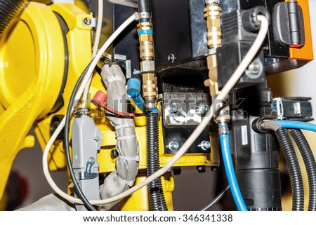 Yellow industrial robot close up with wires - stock photo