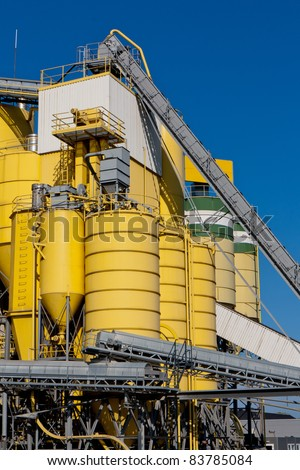 Yellow industrial silos against a blue sky - stock photo