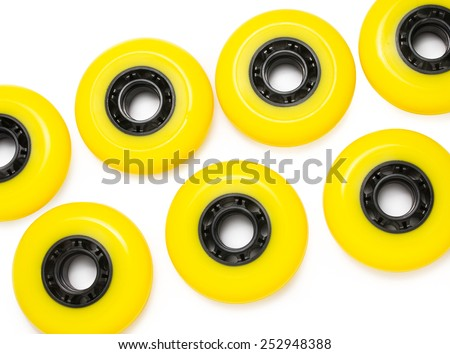 Yellow inline skate wheels laying in random order - stock photo