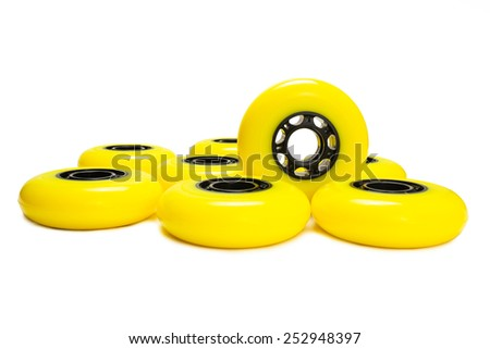Yellow inline skate wheels. One wheel standing. White background. Isolated