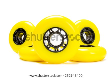 Yellow inline skate wheels standing and laying on white background. Isolated - stock photo