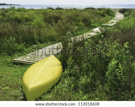 Yellow kayak, upside down, at end of boardwalk to beach - stock photo