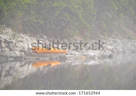 Yellow kayaks sitting on the shoreline of a lake in the fog. - stock photo