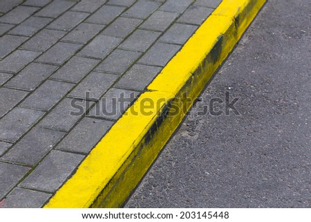 Yellow kerb line on the asphalt proad - stock photo