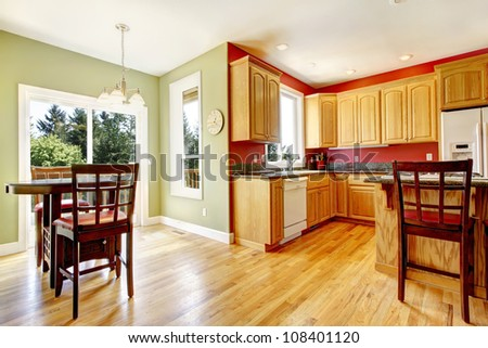 Yellow kitchen with wood and red and green colors with island. - stock photo