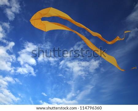 Yellow kite soaring in blue sky - stock photo