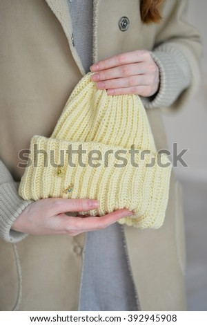 yellow knitted cap in her hand - stock photo