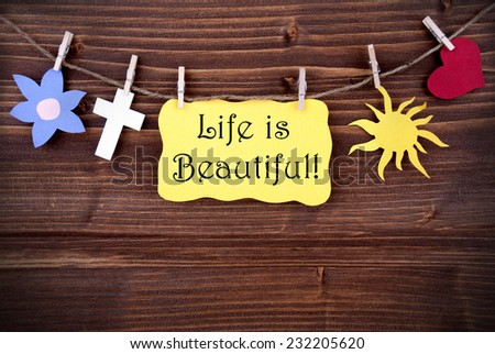 Yellow  Label Saying Life Is Beautiful On Wooden Background With Four Symbols Like Heart, Sun, Cross And Flower - stock photo