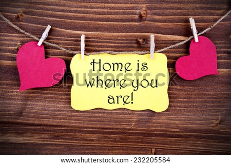 Yellow Lable Saying Home Is Where You Are On Wooden Background Hanging On A Line, Two Red Heart Symbols; On Yellow Label; Background Is Old Fashion - stock photo