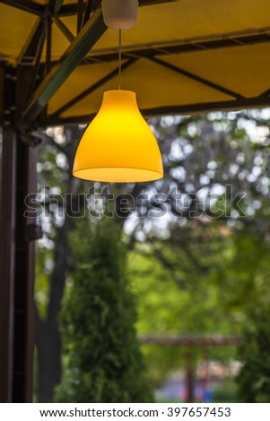 Yellow lamp hanging outside against green forest background