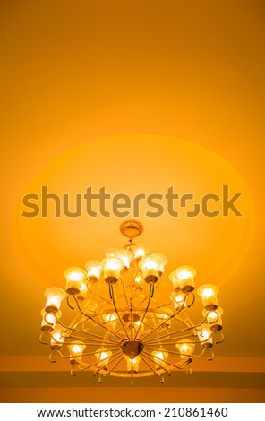 Yellow lamps with brass structure on ceiling in ballroom  - stock photo