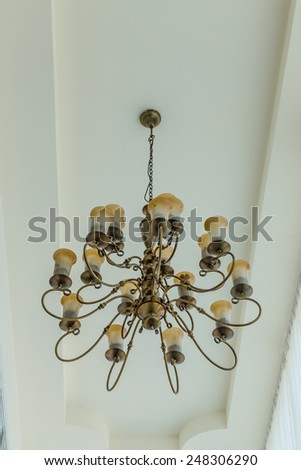 Yellow lamps with brass structure on ceiling in ballroom