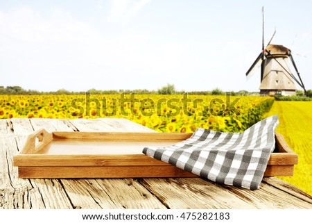 yellow landscape of sunflowers and wind mill with wooden space for your decoration