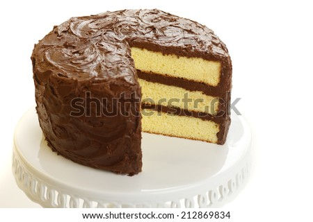 Yellow layer cake with chocolate icing with one slice missing. - stock photo