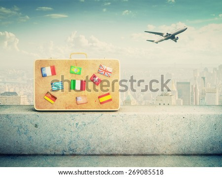 yellow leather suitcase with flag icons - stock photo