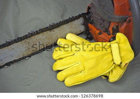 yellow leather work gloves with chainsaw and copyspace - stock photo