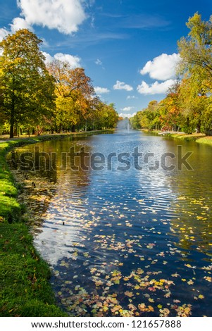 Yellow leaves in the autumn park and river - stock photo