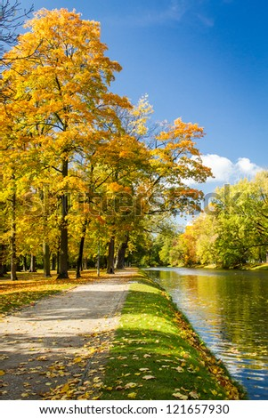 Yellow leaves with blue river in autumn park - stock photo