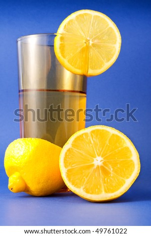 Yellow lemon slices and a glass of lemonade isolated on blue background