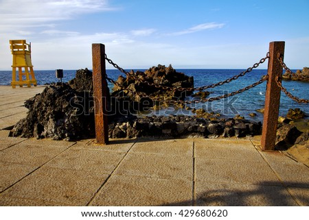 yellow lifeguard chair cabin  in spain  lanzarote  rock stone sky cloud beach  water  musk pond  coastline and summer  - stock photo