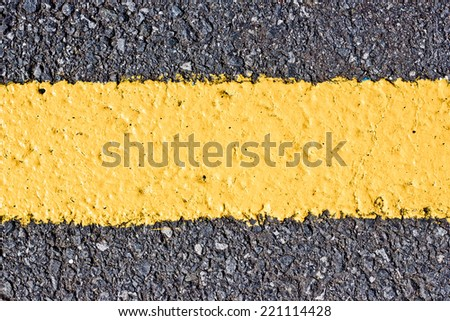 Yellow line painted on asphalt texture.
