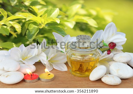 yellow liquid bottle and lily with blur duranta repens background