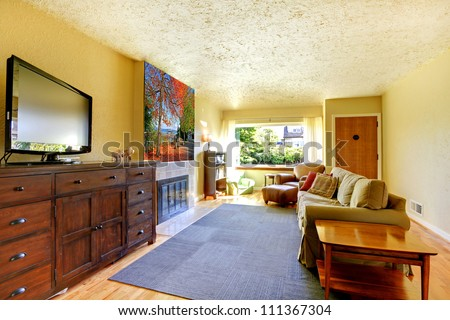 Yellow living room with large dresser with Tv and grey rug. - stock photo
