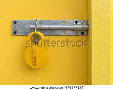 Yellow Locked Padlock and bolt on Yellow Door