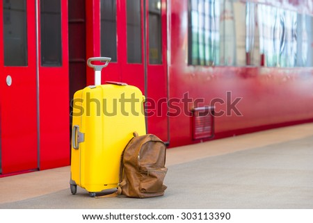 Yellow luggage with passports and brown backpack at train station - stock photo