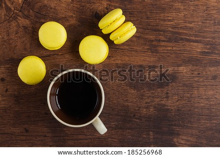 Yellow macaroons with coffee on wooden background - stock photo