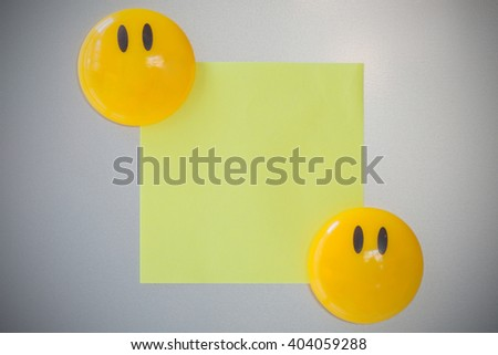 Yellow magnet paper clip lap on yellow paper on gray refrigerator background. - stock photo