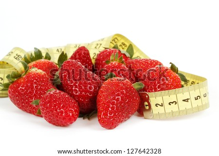 Yellow measuring tape around a strawberry as a symbol of diet