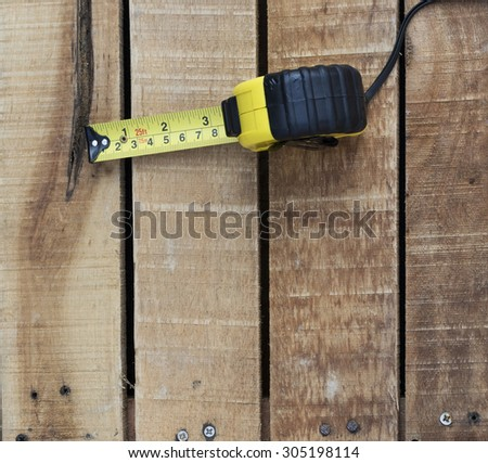 Yellow measuring tape on wooden table - stock photo