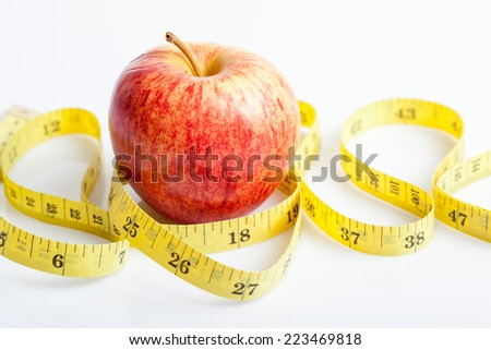Yellow measuring tape with red apple on white background