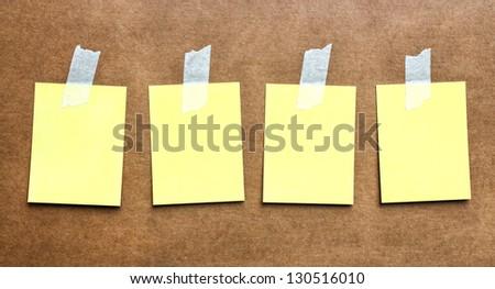 Yellow memo stick on board background - stock photo