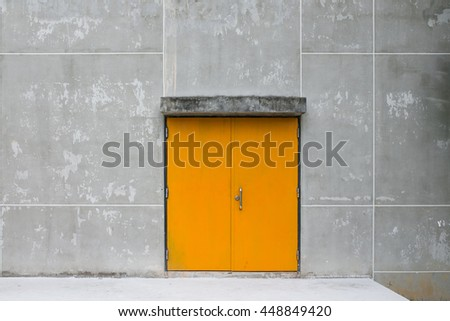 yellow metal door with concrete wall and dirty floor