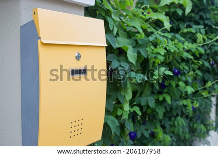 yellow metal mailbox with green leaves background - stock photo