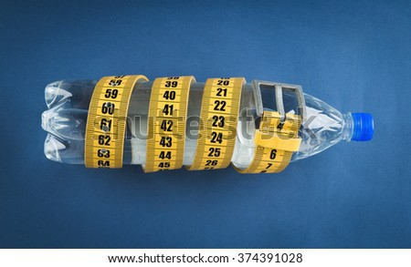 Yellow meter belt slimming and a bottle of water on a blue background - stock photo