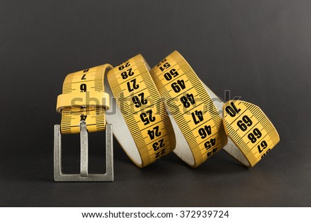 Yellow meter belt slimming on a black - stock photo