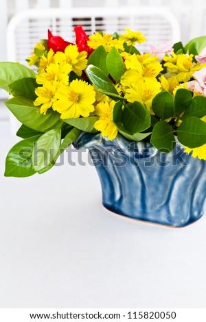 Yellow mexican daisy in blue ceramic vase - stock photo