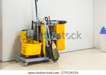 Yellow mop bucket and set of cleaning equipment in the airport - stock photo