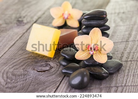 Yellow Moth orchids, black stones and soaps on weathered deck close up - stock photo