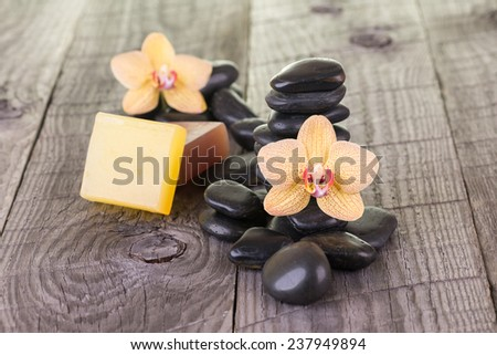 Yellow Moth orchids, soaps  and black stones close up - stock photo