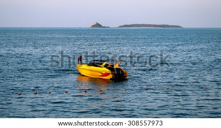 yellow motor boat on the sea on the backdrop of the island