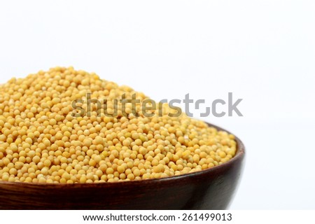 yellow mustard seeds in wooden bowl isolated on white background