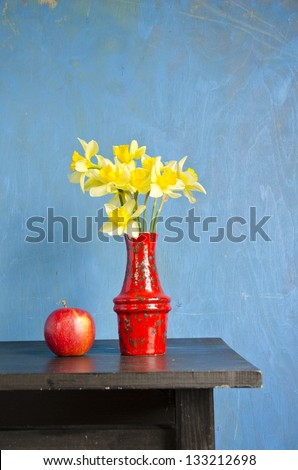yellow narcissus in red vase and apple on black table