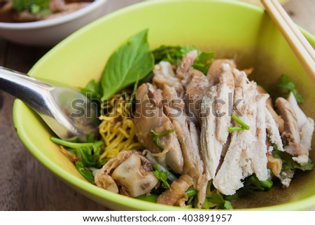 Yellow noodles with chicken boiled and vegetable in a green bowl (Thai Recipe)