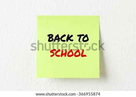 Yellow note paper with words Back to school on the white wall