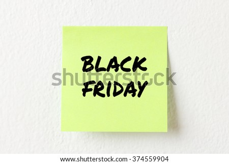 Yellow note paper with words Black friday on the white wall